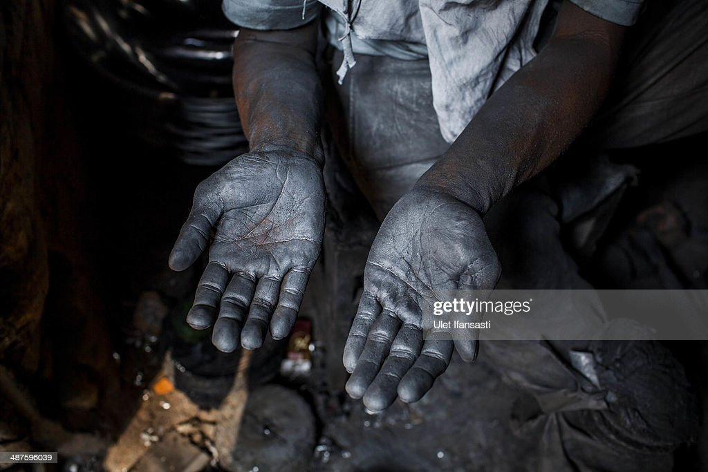 Tarno, a worker shows his hand covered by metal as he work polish a pan at Putra Logam workshop on May 1, 2014 in Yogyakarta, Indonesia. The pan polishers are paid around Rp. 40.000 (USD 3.46) per day. Today is International Labour Day, which aims to bring attention to working conditions, higher wages, and working hours across the world. Protesters across Indonesia have organised rallies to demand higher wages, as Indonesia recognises its first national labour day holiday.