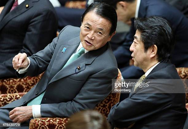 Taro Aso deputy prime minister and finance minister left speaks with Shinzo Abe Japan's prime minister during a budget committee session in the lower...