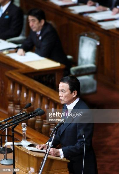 Taro Aso Japan's deputy prime minister and finance minister front delivers his policy speech as Shinzo Abe Japan's prime minister looks on at the...