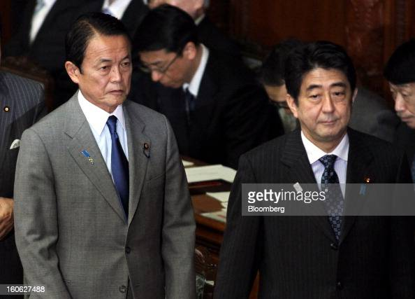 Taro Aso Japan's deputy prime minister and finance minister left and Shinzo Abe Japan's prime minister attend a plenary session at the lower house of...