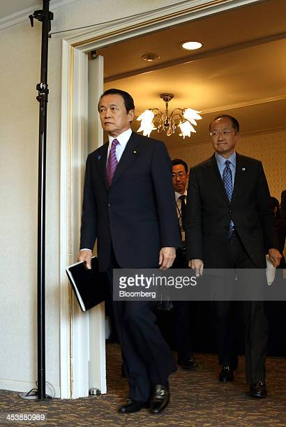 Taro Aso Japan's deputy prime minister and finance minister left and Jim Yong Kim president of the World Bank Group arrive for a news conference at...