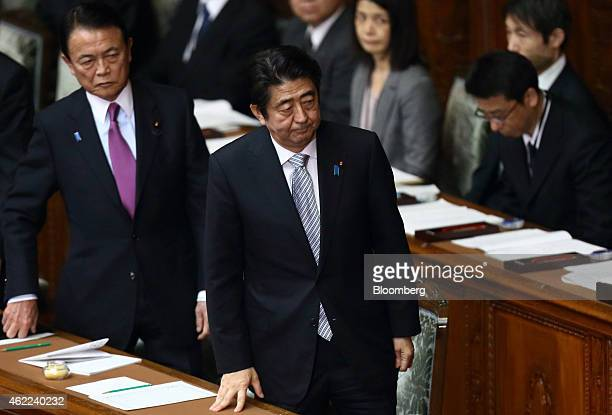 Taro Aso Japan's deputy prime minister and finance minister left and Shinzo Abe Japan's prime minister stand as they leave an ordinary session at the...