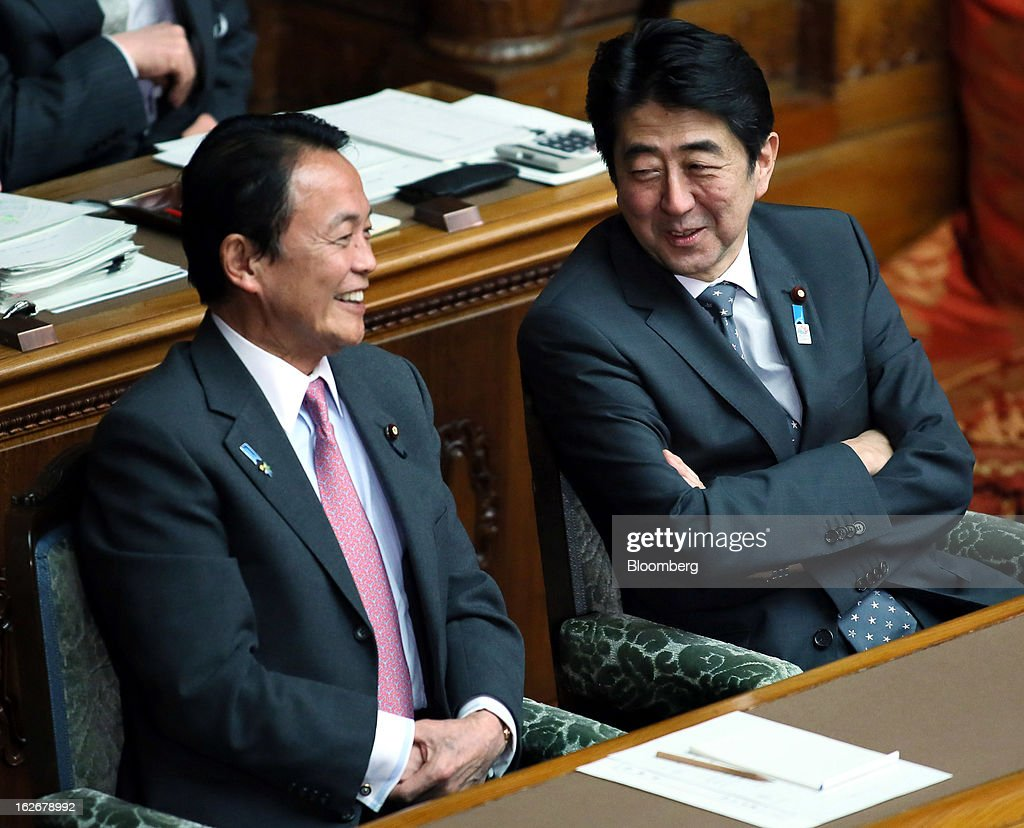 Taro Aso, Japan's deputy prime minister and finance minister, left, speaks to Shinzo Abe, Japan's prime minister, during a plenary session at the upper house of the parliament in Tokyo, Japan, on Tuesday, Feb. 26, 2013. Abe's policies aimed at ending deflation could distort trade, drive up asset prices in other nations and lead to global financial instability, according to HSBC Holdings Plc. Photographer: Haruyoshi Yamaguchi/Bloomberg via Getty Images