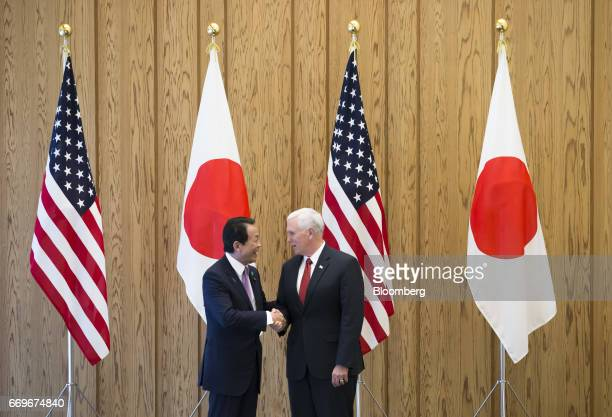 Taro Aso Japan's deputy prime minister and finance minister left shakes hands with US Vice President Mike Pence ahead of their USJapan economic...