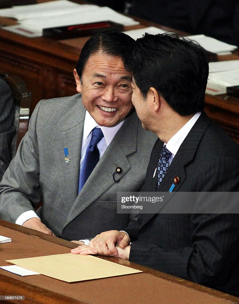 Taro Aso, Japan's deputy prime minister and finance minister, left, speaks with Shinzo Abe, Japan's prime minister, during a plenary session at the lower house of Parliament in Tokyo, Japan, on Monday, Feb. 4, 2013. Aso said Japan will keep monitoring the currency markets carefully. Photographer: Haruyoshi Yamaguchi/Bloomberg via Getty Images