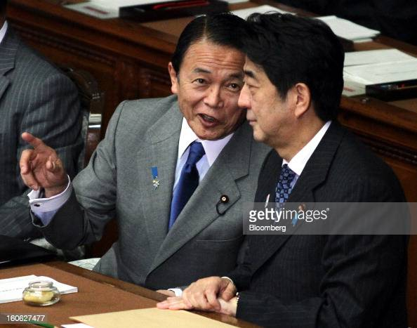 Taro Aso Japan's deputy prime minister and finance minister left speaks with Shinzo Abe Japan's prime minister during a plenary session at the lower...