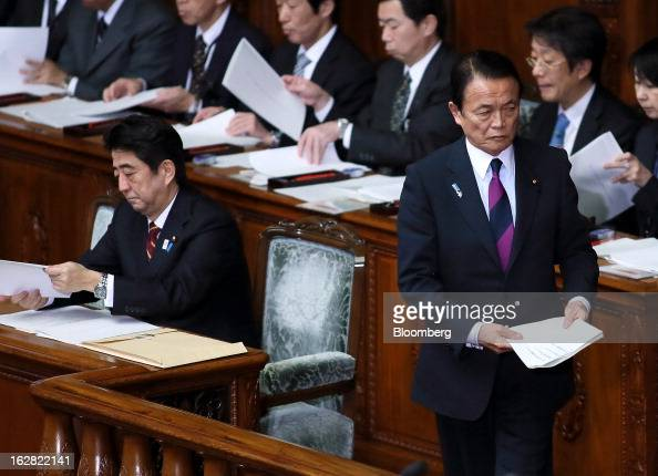 Taro Aso Japan's deputy prime minister and finance minister right prepares to deliver his policy speech as Shinzo Abe Japan's prime minister left...