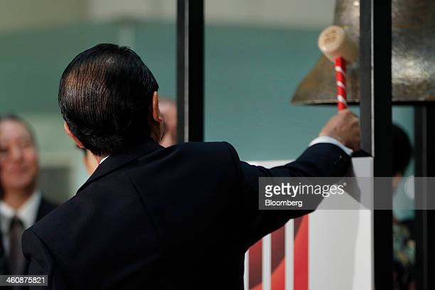 Taro Aso Japan's deputy prime minister and finance minister strikes a bell during a ceremony marking the first trading day of the year at the Japan...