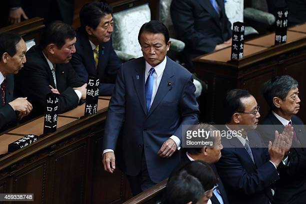 Taro Aso Japan's deputy prime minister and finance minister walks through the lower house of parliament in Tokyo Japan on Friday Nov 21 2014 Japans...