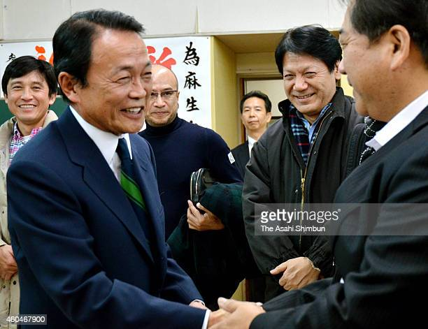 Taro Aso of the Liberal Democratic Party shakes hands with a supporter to celebrate his win in the Fukuoka No8 constituency on December 14 2014 in...