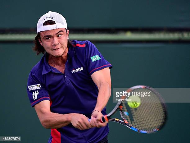 Taro Daniel of Japan plays a backhand against Michael Berrer of Germany during qualifying for the BNP Paribas Open tennis at the Indian Wells Tennis...