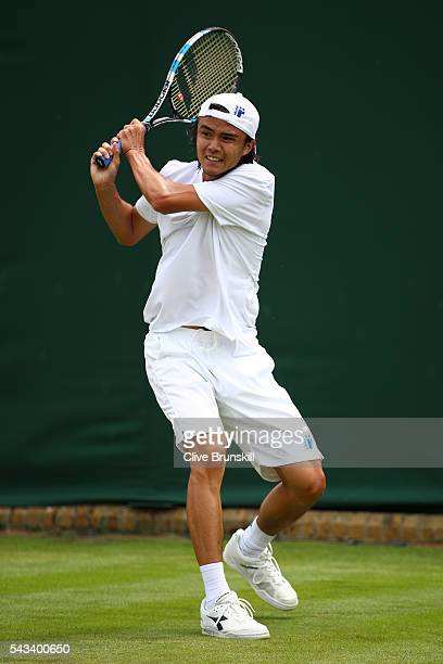Taro Daniel of Japan plays a backhand during the Men's Singles first round match against Juan Monaco of Argentina on day two of the Wimbledon Lawn...