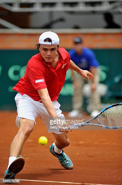 Taro Daniel of Japan returns a backhand shot during the Davis Cup World Group Playoff singles match between Santiago Giraldo of Colombia and Taro...