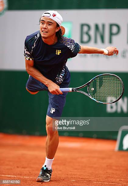 Taro Daniel of Japan serves during the Men's Singles first round match against Martin Klizan of Slovakia on day two of the 2016 French Open at Roland...