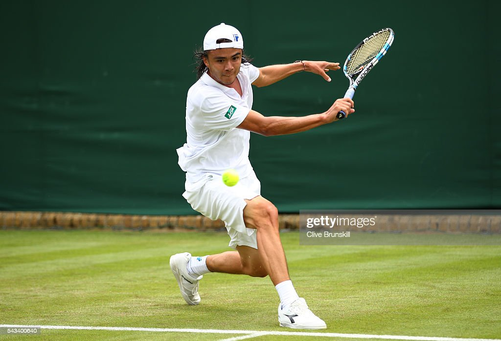 <a gi-track='captionPersonalityLinkClicked' href=/galleries/search?phrase=Taro+Daniel&family=editorial&specificpeople=7180028 ng-click='$event.stopPropagation()'>Taro Daniel</a> of Japan stretches to play a backhand during the Men's Singles first round match against Juan Monaco of Argentina on day two of the Wimbledon Lawn Tennis Championships at the All England Lawn Tennis and Croquet Club on June 28, 2016 in London, England.