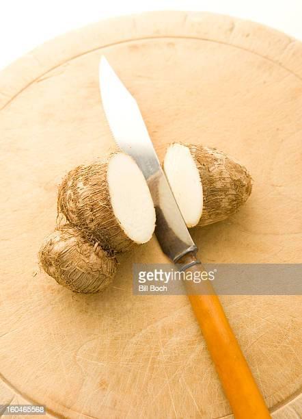 Taro root sliced on a cutting board