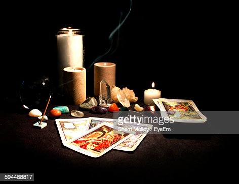Tarot Cards With Lit Candle Against Black Background