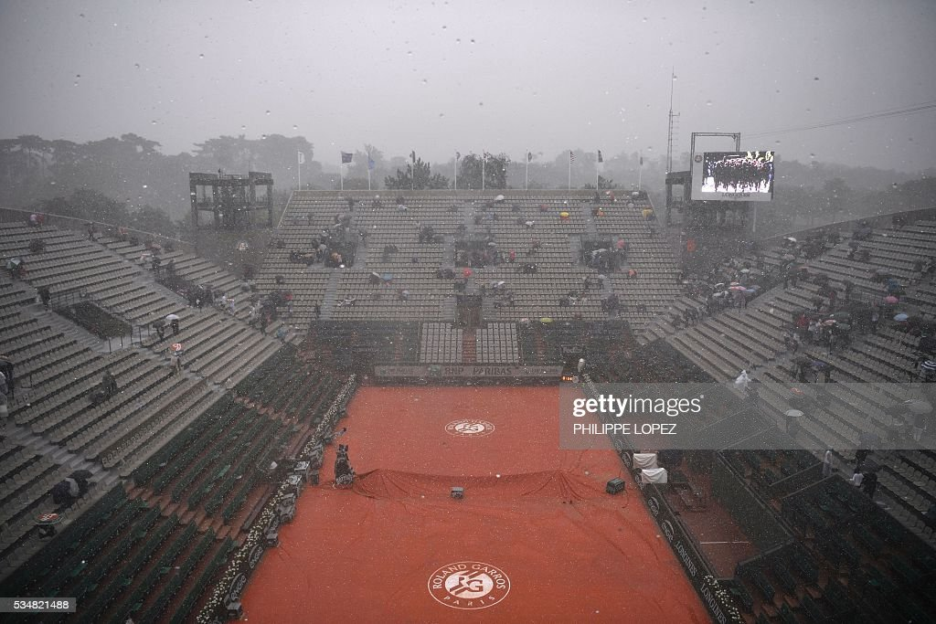 A tarp covers the court as rain interrupts play during the women's third round match between the US's Venus Williams and France's Alize Cornet at the Roland Garros 2016 French Tennis Open in Paris on May 28, 2016. / AFP / PHILIPPE