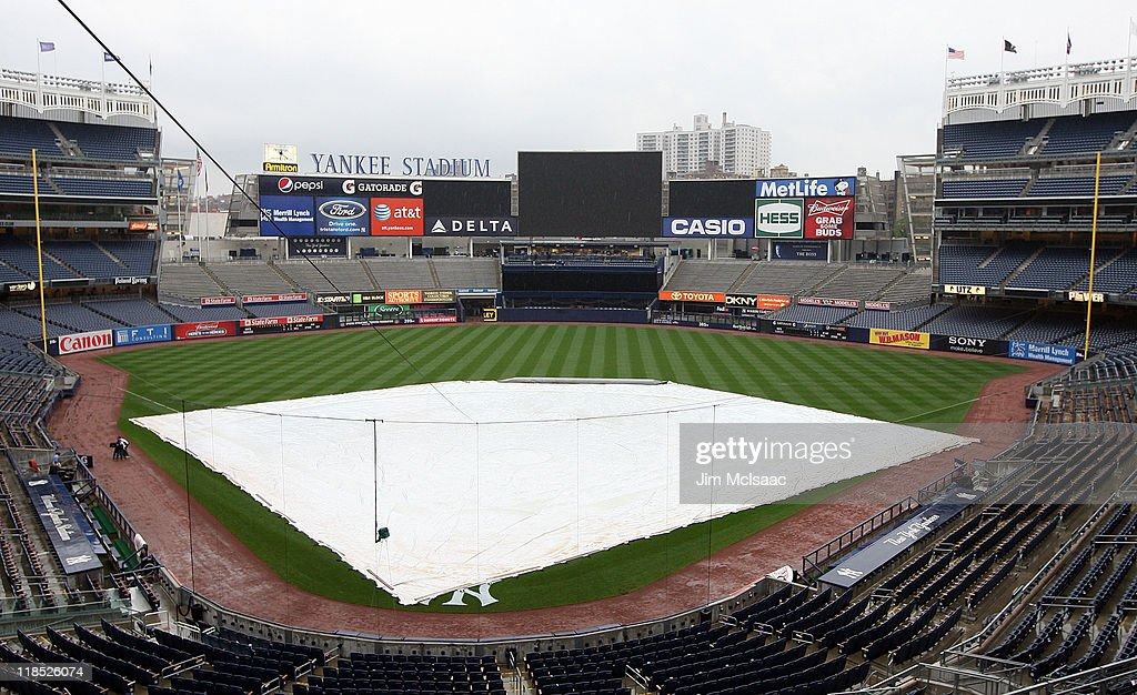 A tarp covers the field as the game between the New York Yankees and the Tampa Bay Rays is postponed due to rain on July 8, 2011 at Yankee Stadium in the Bronx borough of New York City.