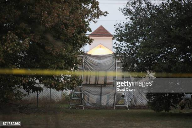 A tarp hangs in front of the Sutherland Springs Baptist church November 8 2017 in Sutherland Springs Texas The tarp was placed in the yard by a local...