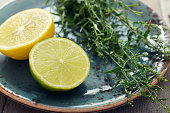 Fresh tarragon with lemon and lime on plate on wooden background