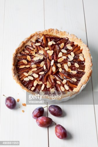 Tart pan with plum cake and plums on white wooden table