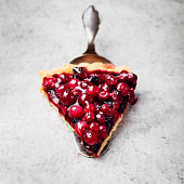 Tart , pie , cake with jellied fresh cranberries, bilberries and winter spices on a grey stone background