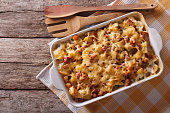 French cuisine: tartiflette potatoes with bacon and cheese close up in baking dish. horizontal top view