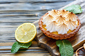Tartlet with Italian meringue and lemon cream on a wooden stand, selective focus.