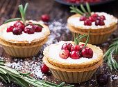 Tartlets of pastry with cream and fresh berries ripe cranberries and rosemary leaves sprinkled with coconut on the texture wooden background. selective Focus