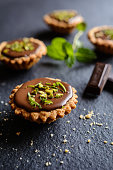 Tartlets with chocolate filling, pistachio and lime peel topping