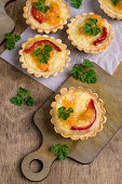 Tartlets with vegetables and cheese on wooden background. Selective focus.
