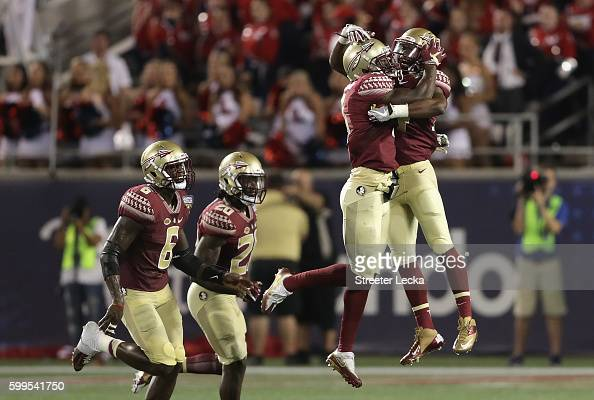 Tarvarus McFadden of the Florida State Seminoles celebrates with teammates after intercepting a pass in the fourth quarter against the Mississippi...
