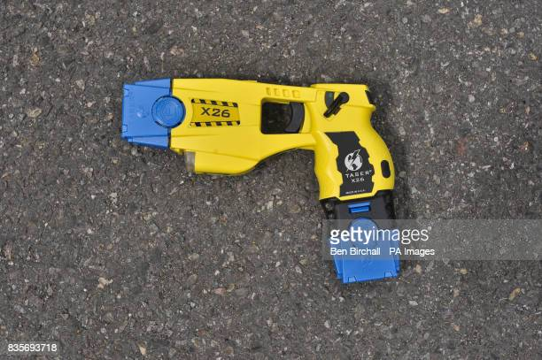 A Taser X26 fitted with two blue training cartriges Areas that can be seen are the firing end white torch light and laser sight trigger safety catch...
