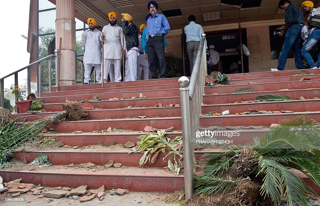 Task force members and employees of the Delhi Sikh Gurudwara Prabhandak (management) Committee (DSPC) look on amid broken pots following clashes at the Rakabganj Sahib Gurdwara in New Delhi on November 15, 2012. Two groups clashed at a Sikh temple in the Indian capital ahead of a Delhi Sikh Gurudwara Prabhandak Committee (DSPC) meeting injuring four people, a local report said. The incident took place at the Rakabganj Sahib Gurdwara when supporters of Paramjeet Singh Sarna and Manjeet Singh clashed. AFP PHOTO/ Prakash SINGH