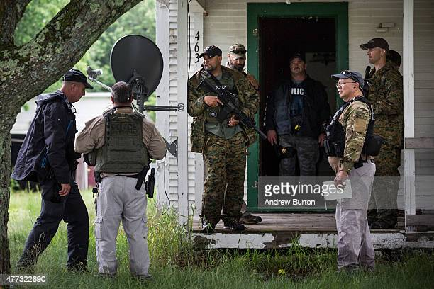 A task force of US Marshalls and police officers go door to door searching for two escaped convicts on June 16 2015 outside Dannemora New York The...