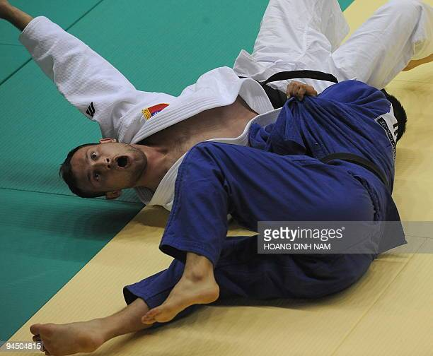 Taslim Johanes of Indonesia celebrates after defeating Aung Moe of Myanmar in the judo men's 81kg event of the 25th Southeast Asian Games being held...