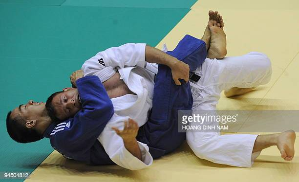 Taslim Johanes of Indonesia fights Aung Moe of Myanmar in the judo men's 81kg event of the 25th Southeast Asian Games being held in Vientiane on...