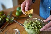 tasting the guacamole, dipping tortilla chip shot with selective focus