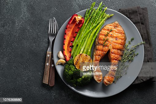Tasty and healthy salmon steak with asparagus, broccoli and red pepper on a gray plate. Diet food on a dark background with copy space. Top view. Flat lay : Stock Photo