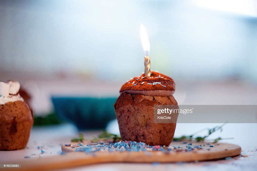 tasty birthday cupcake with candle on the table, blurred background : Stock Photo