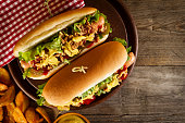 Tasty classic traditional hot dog on wooden board on wooden table background. Top View.