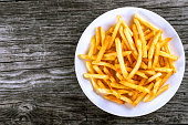 Tasty french fries on white plate, on wooden table background, blank space left, top view