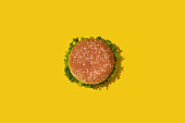 Tasty fresh unhealthy hamburger with ketchup and vegetables on yellow vibrant bright background. Top View with Copy Space. Pattern. Flat lay.