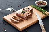 Tasty homemade well-done steak on wooden cutting board with fork and knife on stone background. Sliced roasted pork meat with rosemary and pepper.