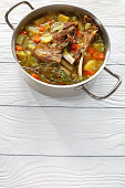 kjotsupa -  Icelandic Lamb winter hot Soup in a stainless steel casserole pan on wooden table, authentic recipe, vertical view from above