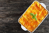 delicious italian lasagna layered with pasta sheets and  bolognese ragout, topped with melted cheese and fresh basil leaves in baking dish on old dark wooden table, horizontal view from above