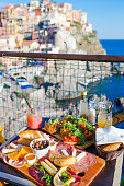 Tasty italian snack. Fresh bruschettes, cheeses and meat on the board in outdoor cafe with amazing view in Manarola