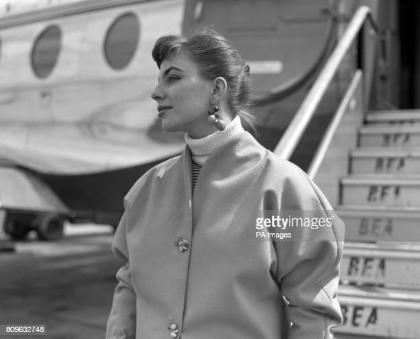 Tasty looking berry earrings are worn by actress Joan Collins pictured as she went aboard a BEA Viscount at London Airport on her way to Rome She...