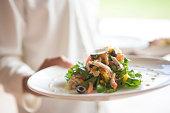 Waiter serving tasty salad for lunch, selective focus